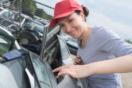 junk yard: Lady in scrap yard by car door