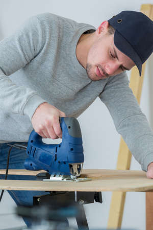 ply: Man using electric jigsaw