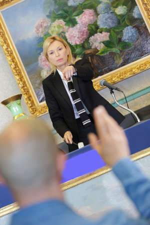 bidder: blond woman auctioneer pointing finger at bidder Stock Photo