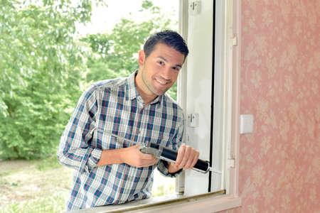 putty: man fixing window Stock Photo