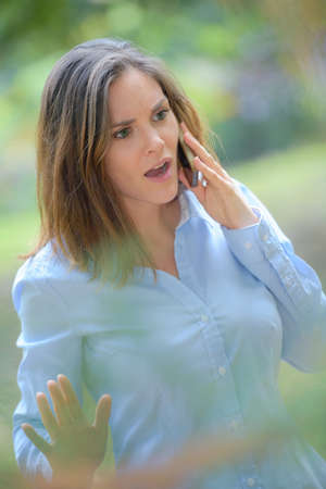 disbelief: Angry woman outdoors on cellphone Stock Photo