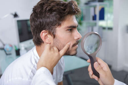malign: close-up of doctors hands checking mans moles Stock Photo