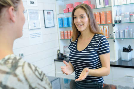 over the counter: Two women talking over cosmetics counter Stock Photo