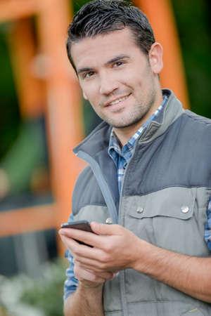 businessman phone: Foreman sending a text message