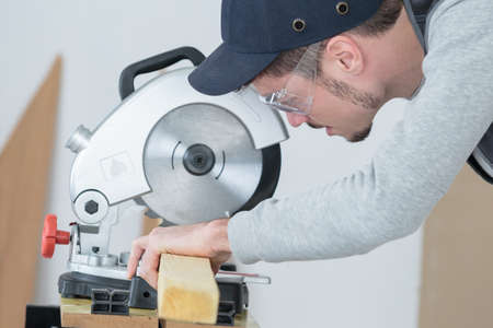 safety googles: carpenter cutting plank of wood with circular disc saw