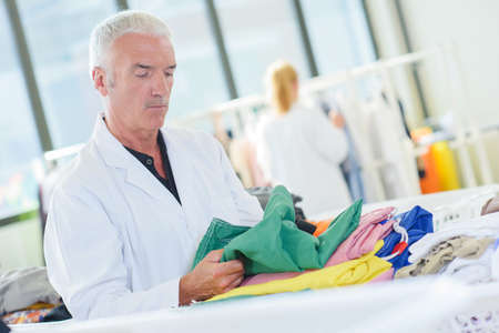 Man inspecting garment in laundry