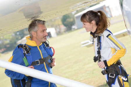 parachutists: Male and female parachutists under wing of aircraft