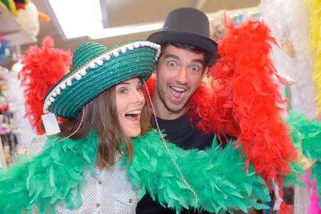 boas: Couple posing in fancy dress hats and boas