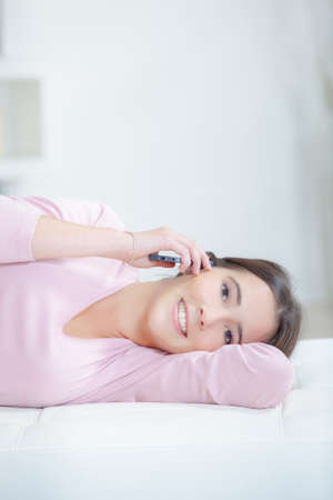 living moment: Young woman relaxing and phoning