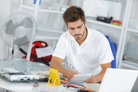 young engineer: young engineer taking notes while developping new induction hobs Stock Photo