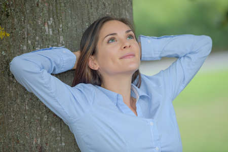 contentedness: Lady leaning back against tree trunk