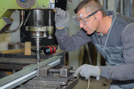 safety googles: worker drilling metal with a large drill in a workshop Stock Photo