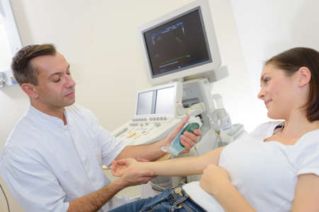 medical scanner: Doctor preparing to scan patients arm Stock Photo