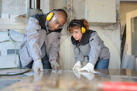 safety googles: co-workers varnishing wooden panels in workshop