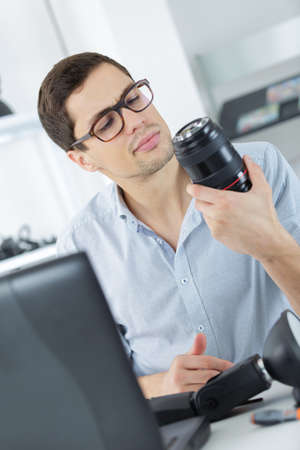 engineering tool: male repairing a camera at his workplace Stock Photo