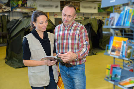 sales assistant showing customer tents catalog in outdoors store Stock Photo