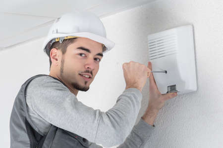 screwing: Worker screwing alarm to wall