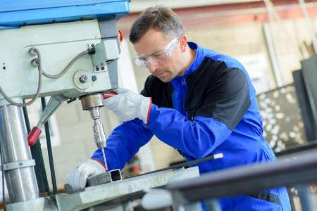 pierce: Workman drilling through square steel bar Stock Photo