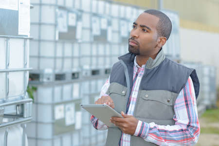 vats: Worker holding tablet inspecting vats