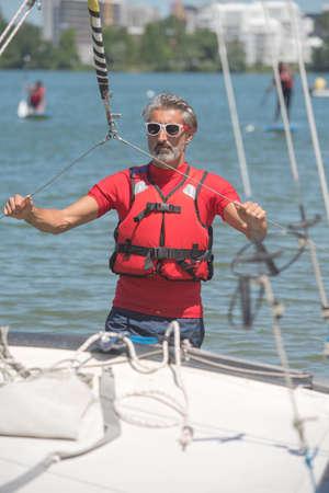 lifevest: portrait of mature sportsman near catamaran