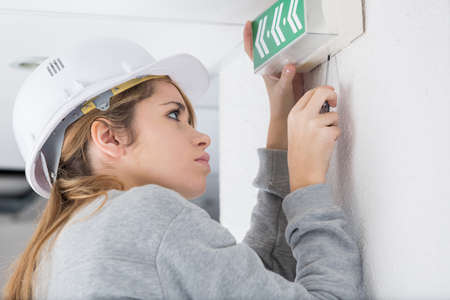 screwing: Woman screwing directional exit sign to wall