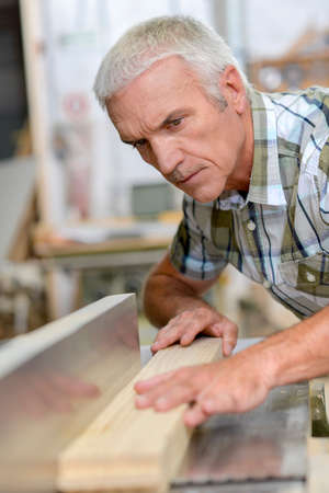 whilst: Concentrating whilst using a table saw Stock Photo