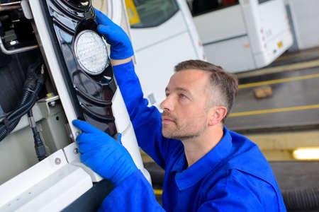 Travailleur d'installer la lumière de bus Banque d'images - 70778483
