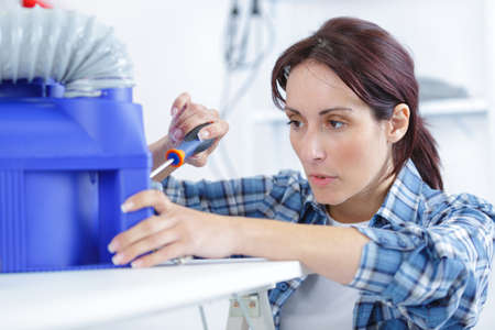 office tool: woman using screwdriver diy enthusiast Stock Photo