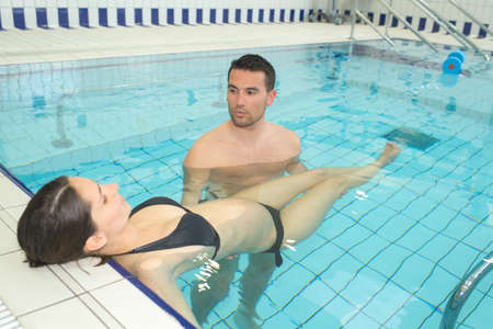 afloat: Man holding woman afloat in swimming pool Stock Photo