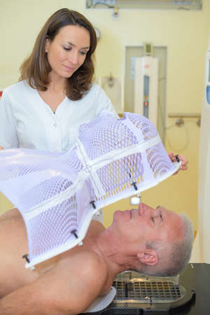 radiotherapy: nurse putting mask on patient before radiation therapy Stock Photo