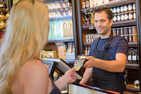 pagando: Mujer que paga las purchaces en una tienda de delicatessen