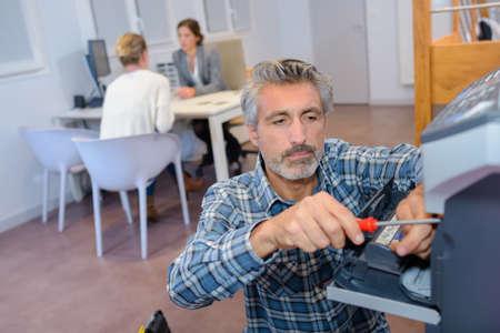 technical department: company handyman fixing a printer