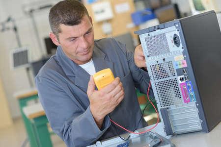 Repairman testing computer with multimeter