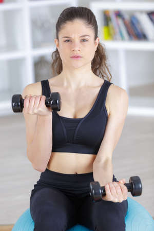 fitness model brunette holding weights Stock Photo