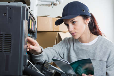 information equipment: Lady with instruction book working on photocopier