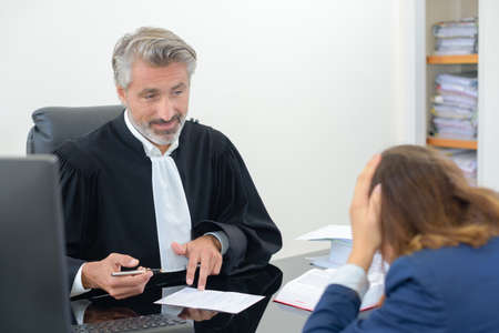 despondency: Client with head in hands talking to lawyer Stock Photo