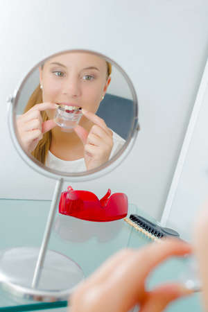 office tool: Woman inserting a mouth guard Stock Photo