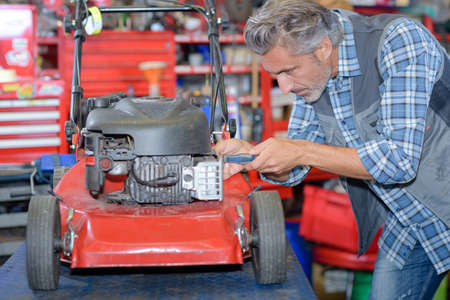 to maintain: worker fixing the lawn mower Stock Photo
