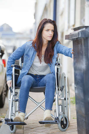 Woman in wheelchair struggling to pass obstruction