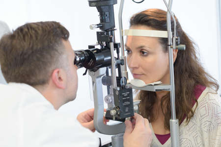 testing vision: Optician testing female patient