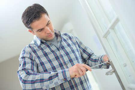 screwing: Man screwing on door handle Stock Photo
