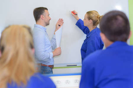 Student at board with teacher, writing Stock Photo