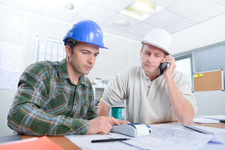 looking over: Two architect looking over plans Stock Photo