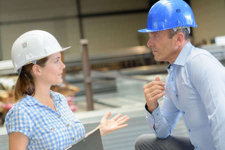 animosity: Man and woman in workplace wearing hardhats