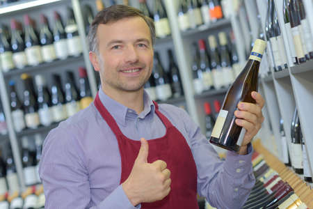 retailer: Retailer holding bottle of wine and making positive gesture Stock Photo
