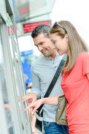 Couple buying travel ticket from machine Stock Photo