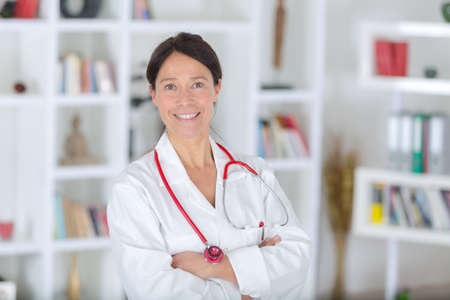 smiling beautiful woman in white medical uniform and stethoscope