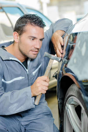 tapping: man with hammer tapping car