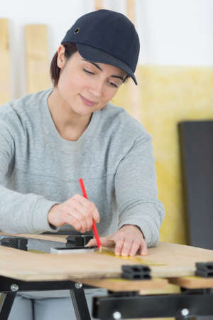 stoop: portrait of happy female woodworker drafting new project at workshop Stock Photo