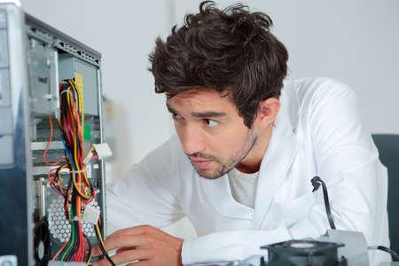 Computer repairman looking confused